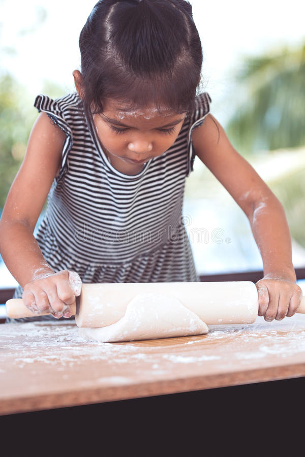 Cute asian little child girl prepares a dough for baking cookies stock photo