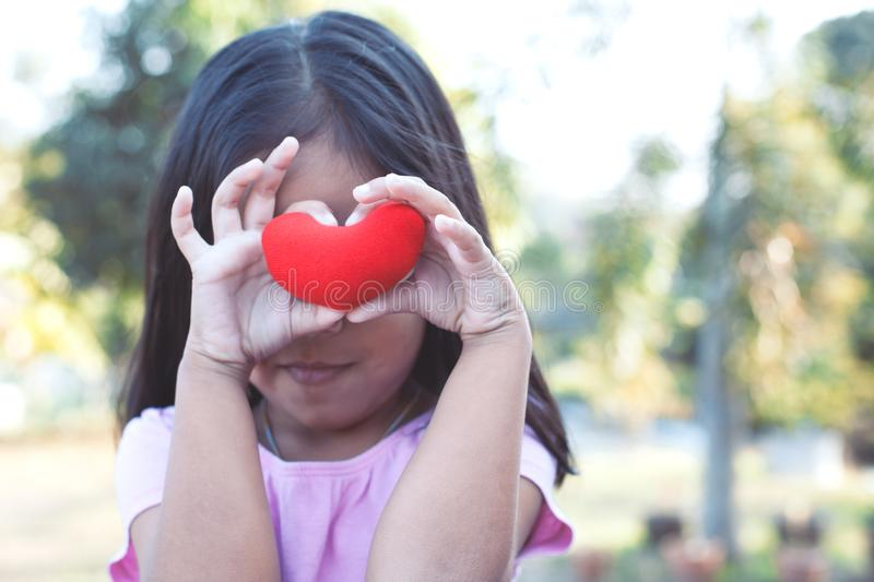 Cute asian little child girl with red heart on the eyes royalty free stock photo
