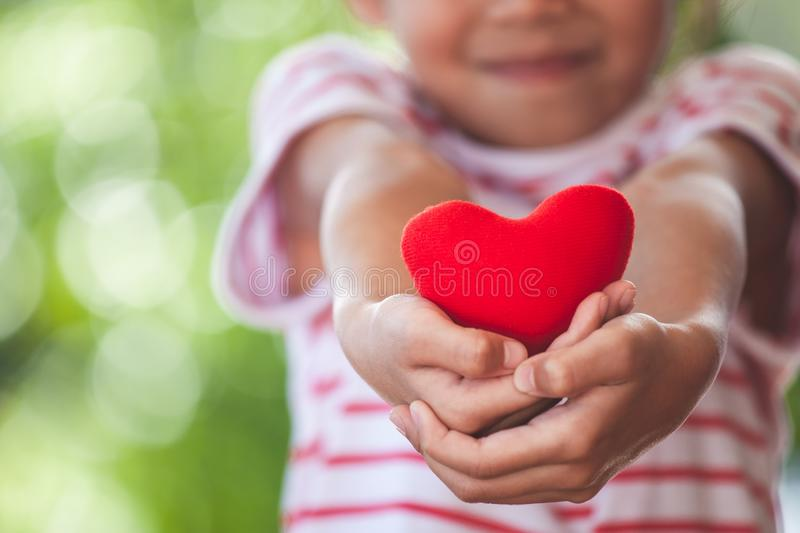 Cute asian little child girl showing and holding red heart in hand. With care and love royalty free stock image