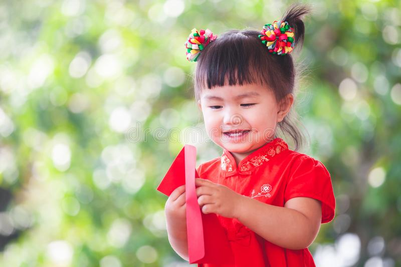 Cute asian child girl smiling and getting money in red envelope and wishing you a happy in Chinese New Year stock photography