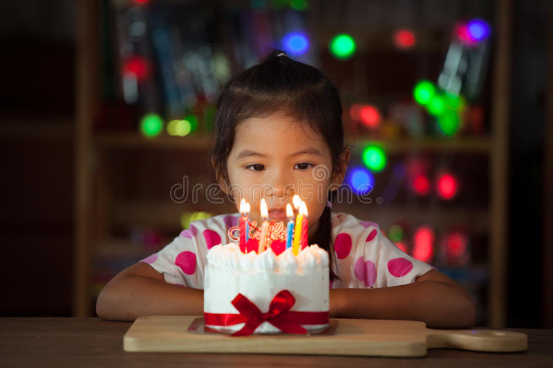 Cute asian little girl with birthday cake in birthday party stock photo