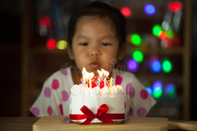 Cute asian little girl celebrating birthday and blowing candles royalty free stock photography