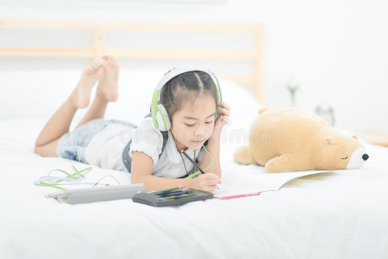 Cute asian little girl doing homework,writing with colourful pen royalty free stock images