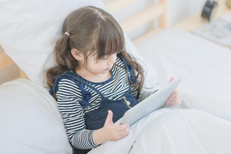 Cute asian little girl enjoy watching cartoon on smart tablet stock photography