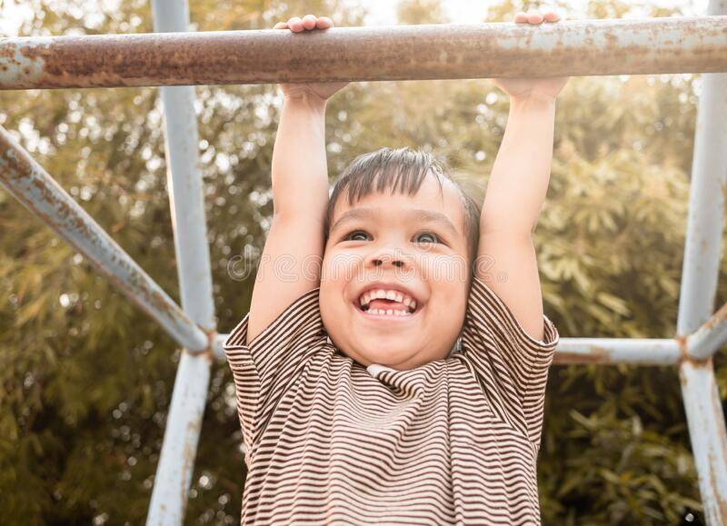 Cute Asian little girl hanging the monkey bars by her hand to exercise at outdoor playground on sunny day royalty free stock photo