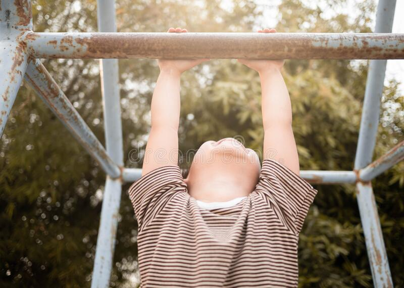 Cute Asian little girl hanging the monkey bars by her hand to exercise at out door playground on sunny day.  stock image