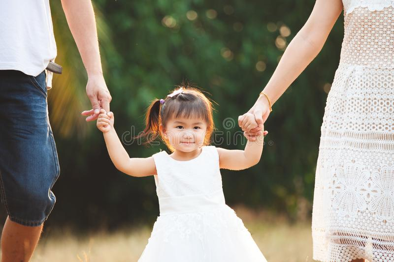 Cute asian little girl holding hand and walking with her parents in the park royalty free stock images