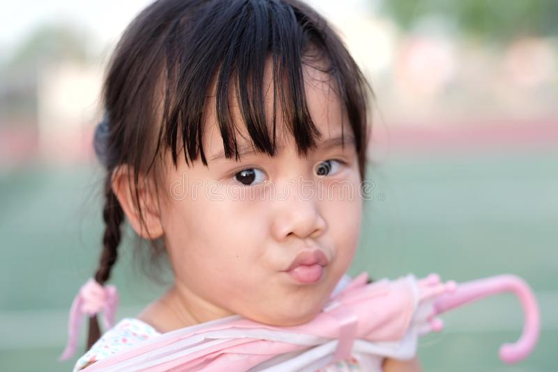 Cute Asian little girl making funny face while took the chin to hold the pink umbrella royalty free stock photos
