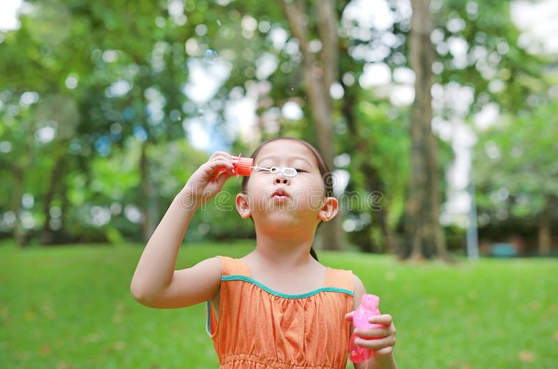 Cute Asian little girl playing bubble in summer park stock photo