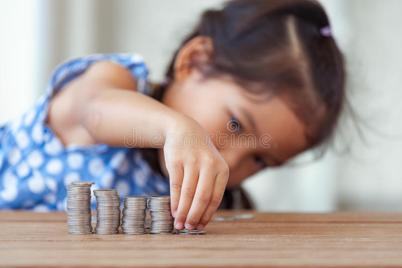 Cute asian little girl playing with coins making stacks of money stock image