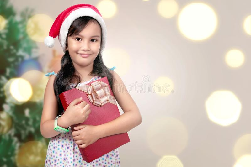 Cute asian little girl with santa hat holding xmas gift box stock photography