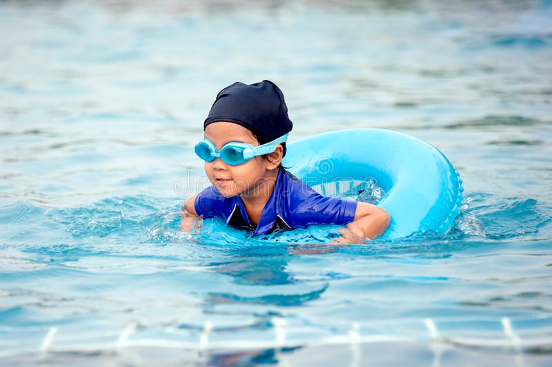 Cute asian little girl with swim ring is having fun to swim. In swimming pool stock images