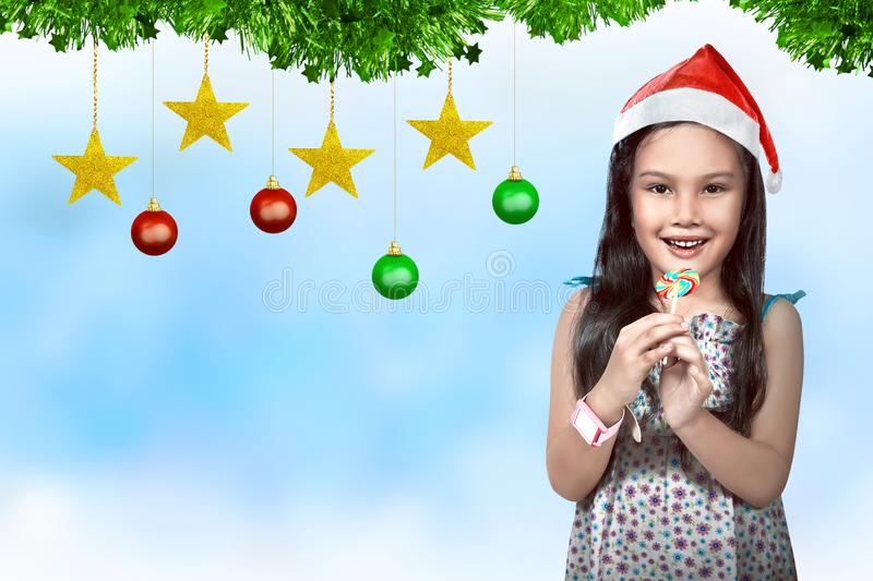 Cute asian little girl wearing santa hat with christmas decoration stock photos