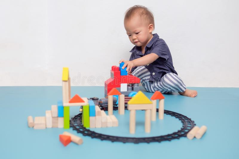 Cute Asian 20 months / 1 year old toddler baby boy child play with colorful wooden blocks stock photos