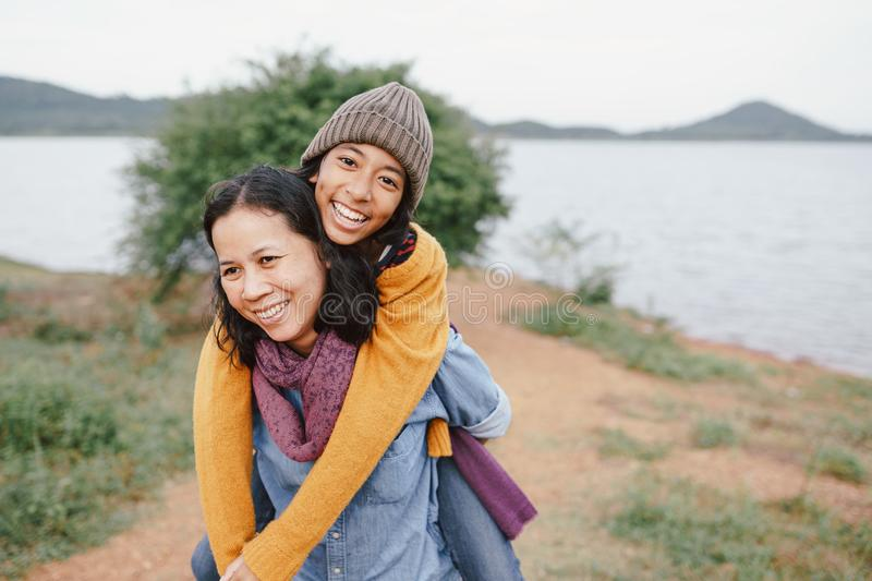 Cute Asian mother and daughter  piggyback ride on her back with the laughing  at river in the morning. The concept of  family  tou stock image