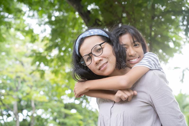 Cute Asian mother and daughter playing and  giving ride on back together at  park, Happy family concept stock image