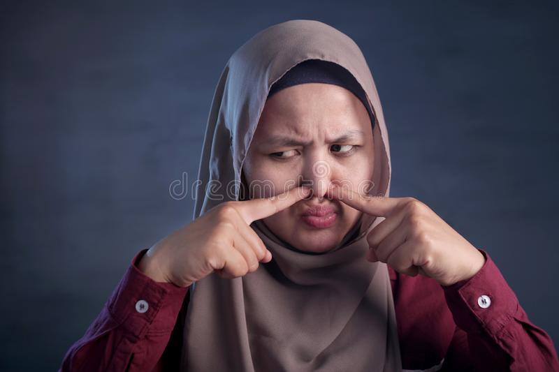 Cute Asian Muslim Lady Close Her Nose. Portrait of cute funny Asian muslim lady wearing hijab close her nose because of bad disgusting smell odor, indonesian royalty free stock images