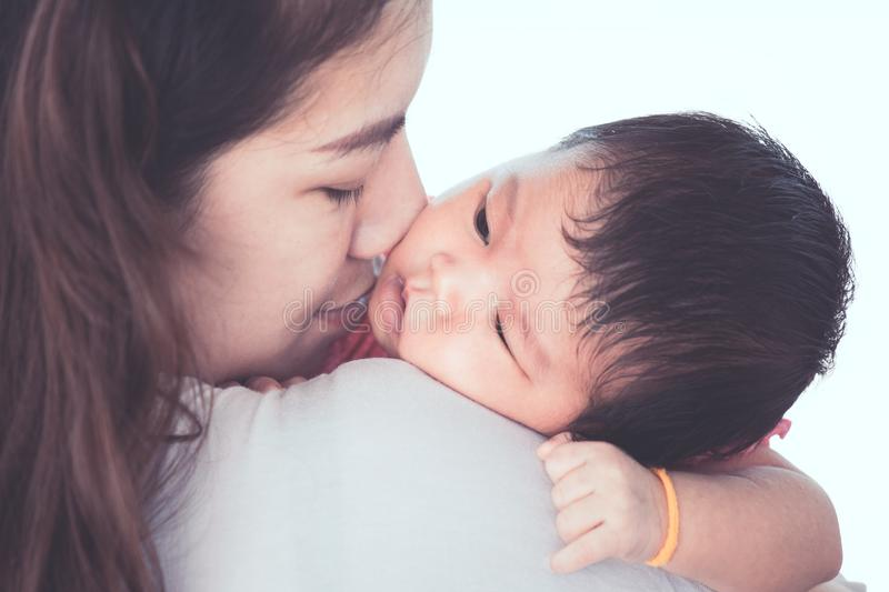 Cute asian newborn baby girl resting on mother`s shoulder. royalty free stock image