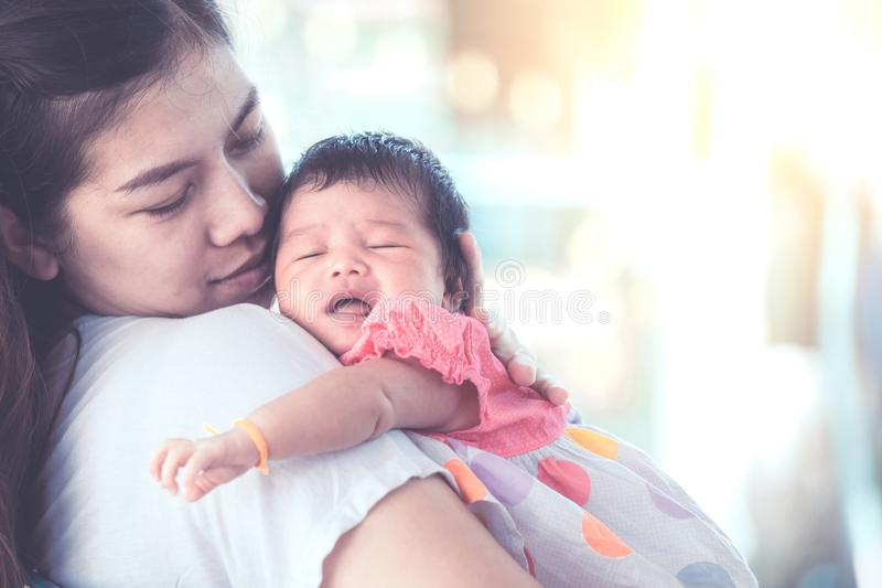 Cute asian newborn baby girl sleeping on mother`s shoulder. Young mother cuddling baby with tenderness stock photography