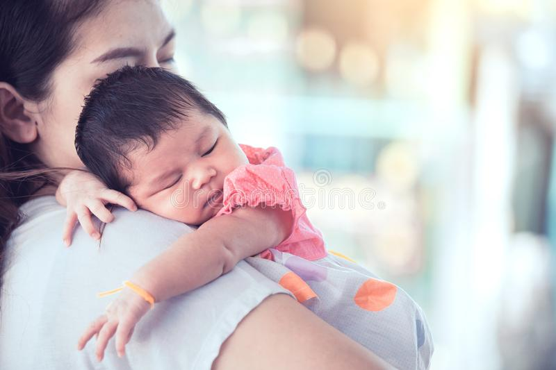 Cute asian newborn baby girl sleeping on mother`s shoulder. Young mother cuddling baby with tenderness royalty free stock photos