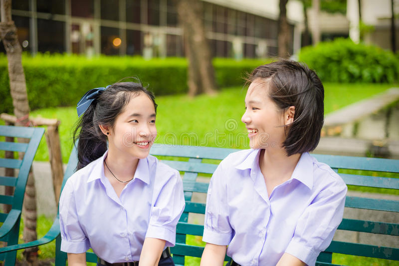 Cute Asian Thai high schoolgirls student couple chatting stock photography