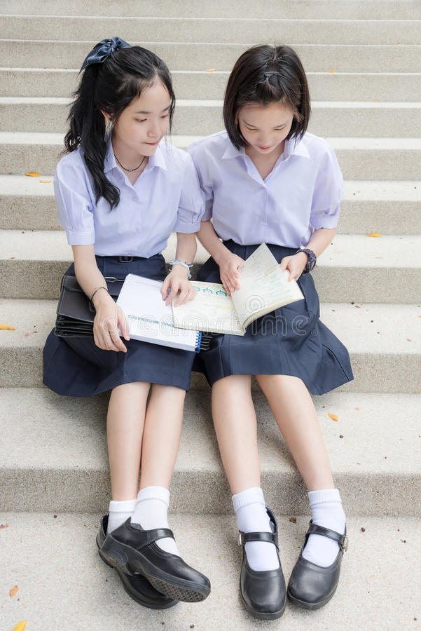 Cute Asian Thai high schoolgirls student couple reading stock images