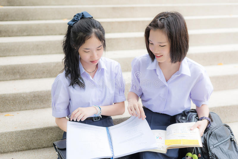 Cute Asian Thai high schoolgirls student couple studying in school stock image