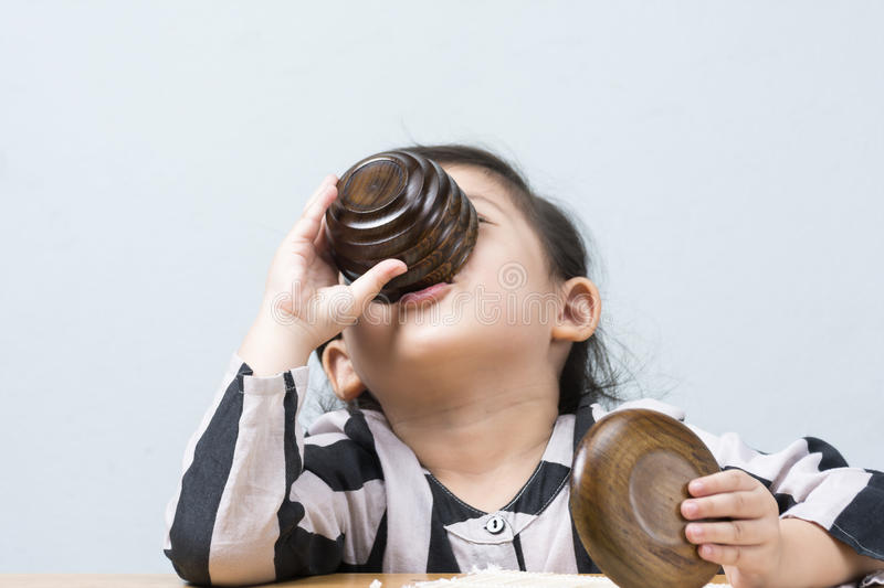 Cute Asian Thai Little Girl Drinking Water from Tea Cup. stock images