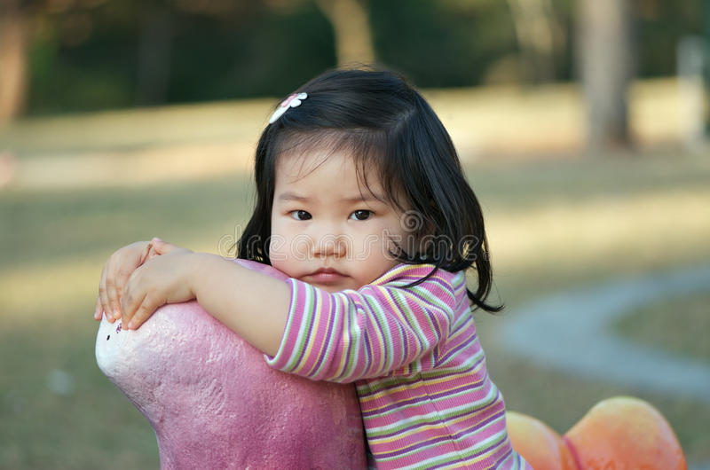Cute Asian toddler. Natural portrait of sweet shy little Asian toddler girl holding onto toy in playground Check out my stock photography