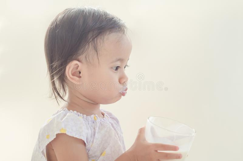 Cute asian toddler girl drinking milk from big glass on white ba. Ckground stock photos