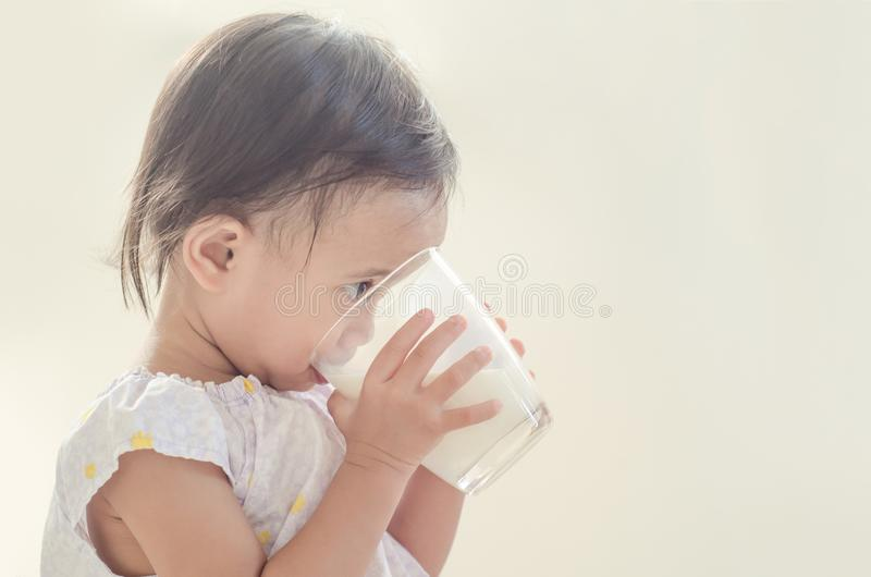 Cute asian toddler girl drinking milk from big glass on white ba. Ckground stock photo