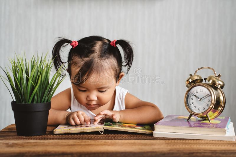 Cute asian toddler reading a book with alarm clock. Concept of early education, parenting, child learning, growth and development stock image