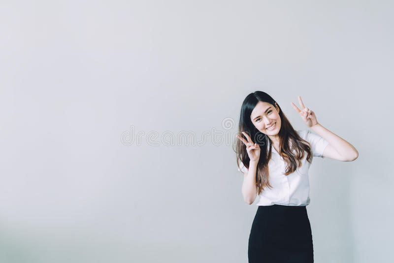 Cute asian university girl doing funny rabbit pose, copy space on gray wall background royalty free stock images