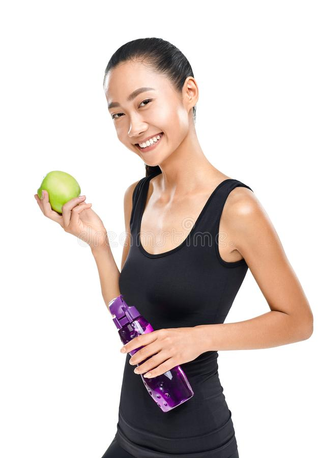 Cute Asian woman holding green Apple and sports water bottle stock image