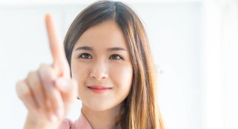 Cute Asian woman pushing on a touch screen windows stock photos