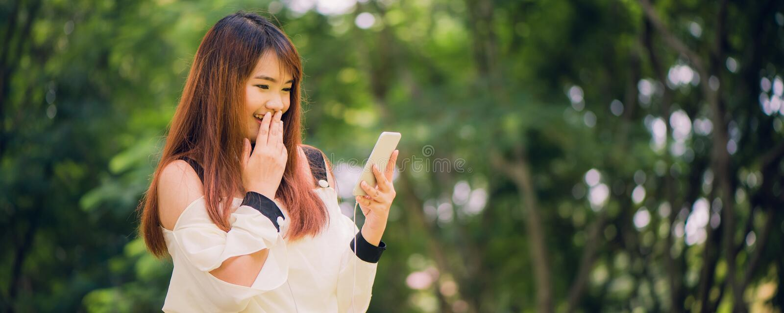 Cute asian woman is reading pleasant text message on mobile phone while sitting in park stock photo