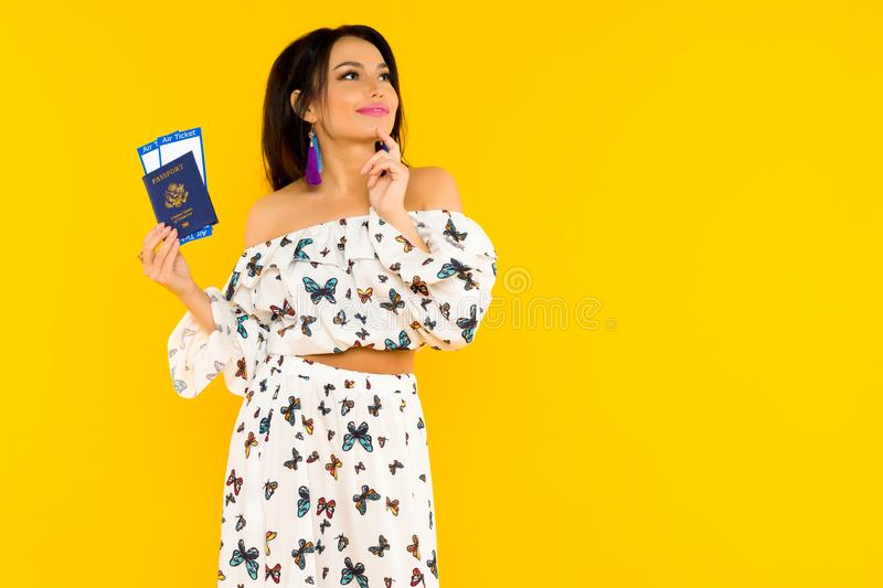 A cute Asian woman in a silk dress with butterflies is holding a passport and air tickets on a yellow background royalty free stock photos
