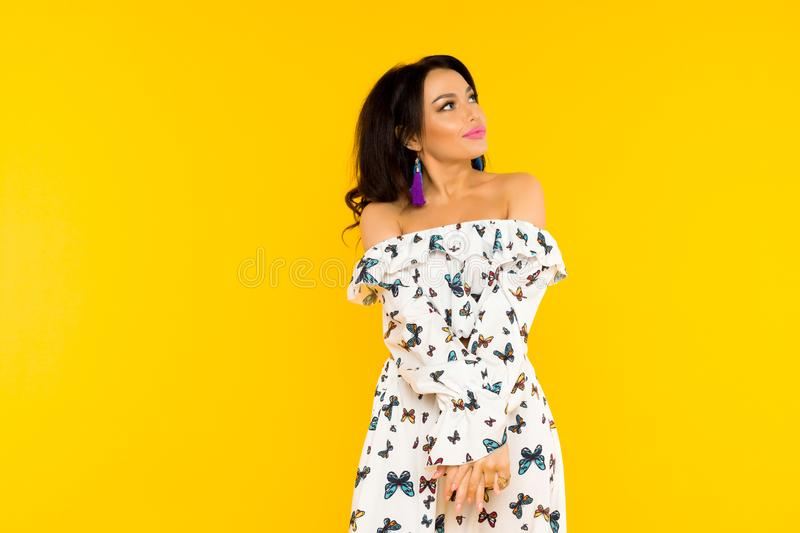 Cute asian woman in silk dress with butterflies posing on yellow background royalty free stock photography