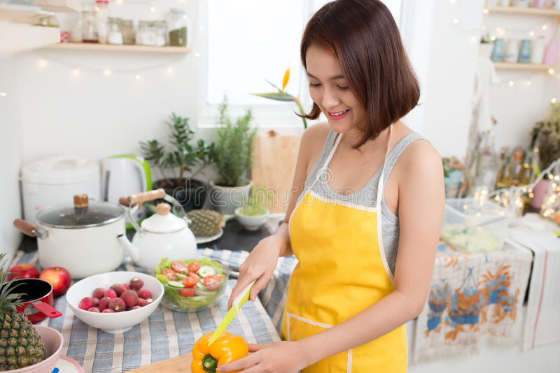 Cute asian woman slicing a pepper in her kitchen stock photography