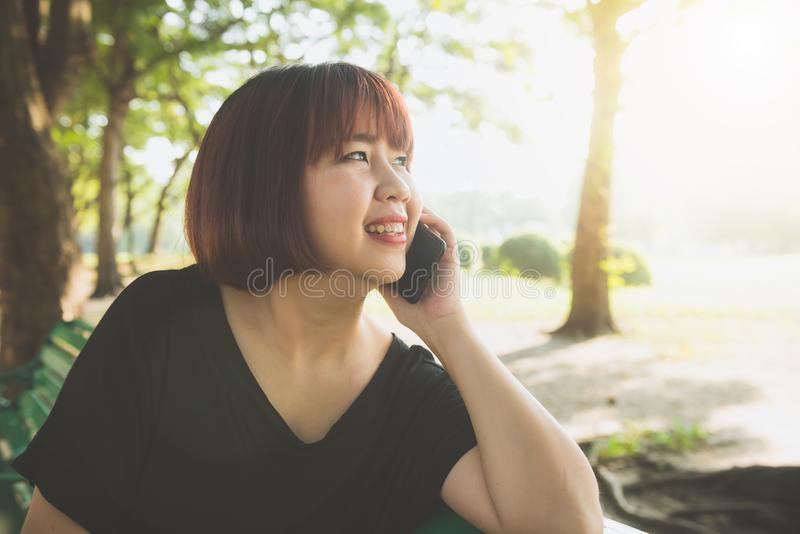 Cute asian woman smiles and talking on mobile phone while sitting in park spring day. stock image