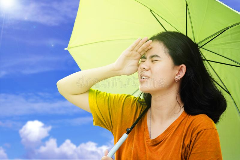 Cute asian women use their hands to covers her face from the sun and holding umbrella with sunlight and blue sky and Cloud backgro stock photography