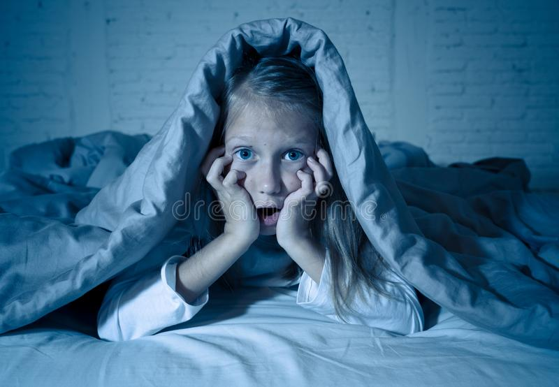 Beautiful little girl awake from a nightmare afraid and suffering fear of dark stock images