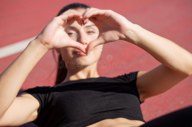 Cute athletic girl making heart symbol from her fingers, lying at the stadium stock image