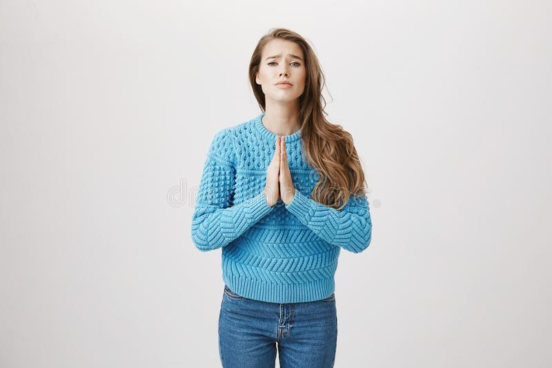 Cute attractive european adult woman standing in begging pose with hands in pray and bending at camera with sad look. Over gray background. Girl asks coworker stock photo
