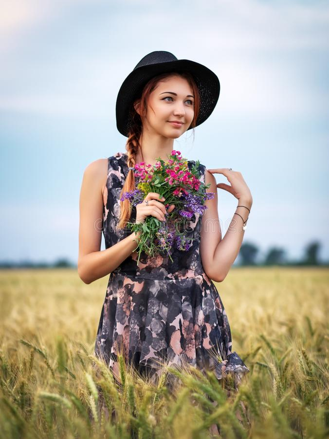 Cute attractive girl with a bouquet of colorful flowers in her hands. Young woman breathes in the scent of plants on wheat field royalty free stock images
