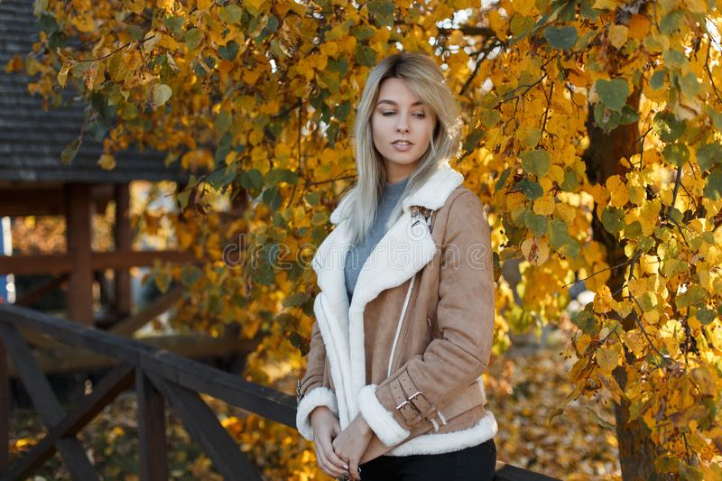 Cute attractive young girl blonde in stylish clothes walks in the park. Autumn, season, people concept stock photos