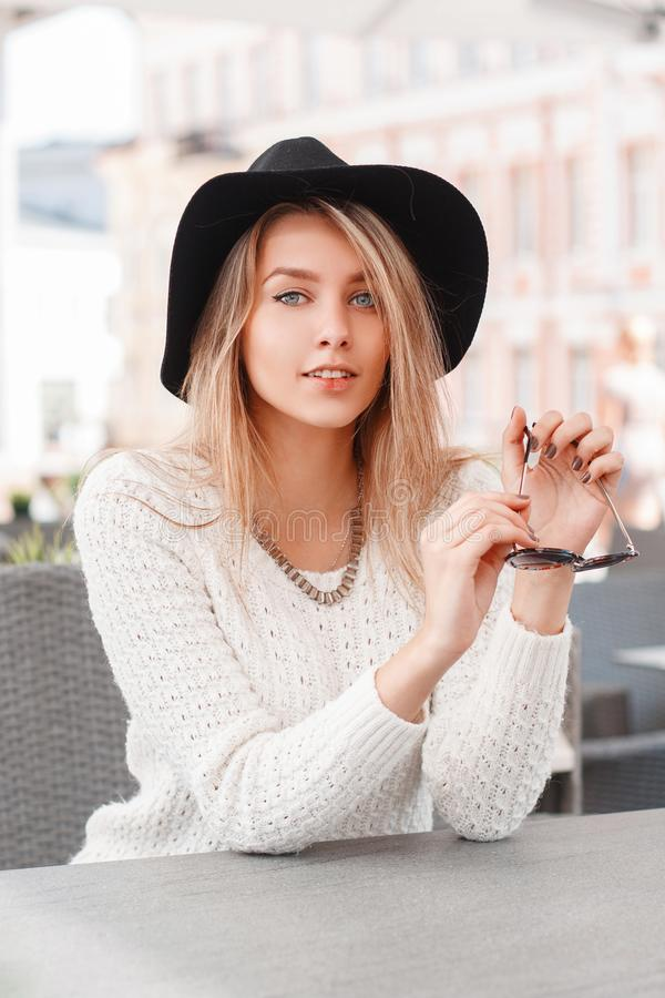 Cute attractive young woman in a white vintage knitted sweater in an elegant hat sitting on a warm spring day in an outdoor cafe. stock image
