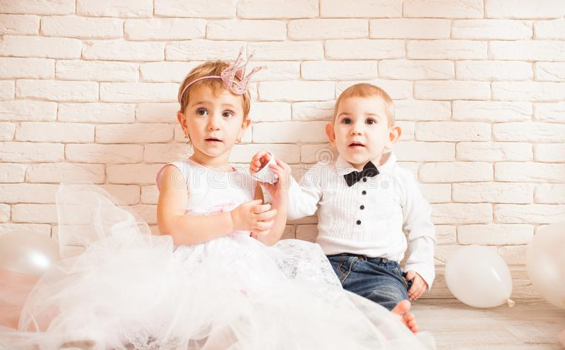 Love relationship metaphor. Cute babies - boy and girl in wedding dress. Concept of love relationship, womens initiative royalty free stock photography