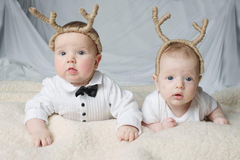 Cute babies with deer horns stock image