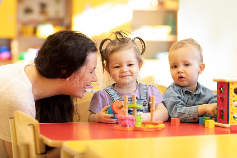 Cute babies play with carer or babysitter in nursery or kindergarten stock photo